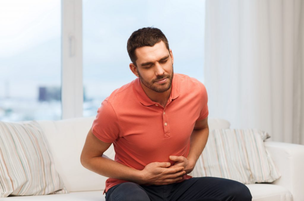people, healthcare and problem concept - unhappy man suffering from stomach ache at home